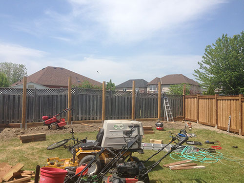 Full privacy wood fence during installation by wholesale fence